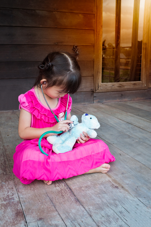 plush toy: Adorable asian child playing doctor or nurse with plush toy bear with bright sunlight at home. Happy girl listens a stethoscope to toy. Playful girl role playing.