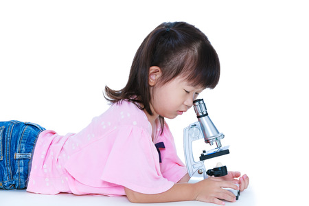 Lovely asian child observed through a microscope biological preparations. Pretty girl having education activities. Isolated on white background.