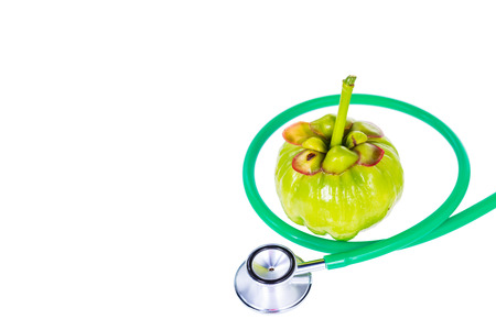 citric: Garcinia cambogia fresh fruit and stethoscope, isolated on white. Garcinia atroviridis is a spice plants and high vitamin C and hydroxy citric acids (HCA) for diet and good health. Stock Photo