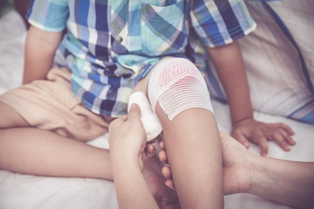 injurious: Child injured. Mother bandaging sons knee. Shallow depth of field (DOF), selective focus, bandage in focus. Human health care and medicine concept. Vintage tone effect.