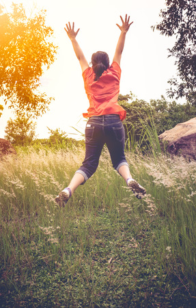 natural light: Back view of woman jumping at forest, outdoor with bright sunlight at the daytime on vacation. Happiness and freedom concept. Vintage tone.