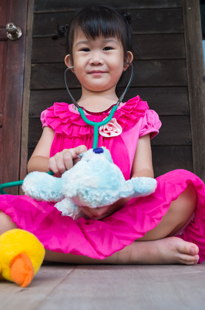 plush toy: Adorable asian child playing doctor or nurse with plush toy bear at home. Happy girl listens a stethoscope to toy. Playful girl role playing.