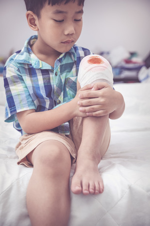Closeup child injured on bed in bedroom. Worry asian handsome boy looking at wound on his knee with bandage. Human health care and medicine concept. Vintage tone effect.
