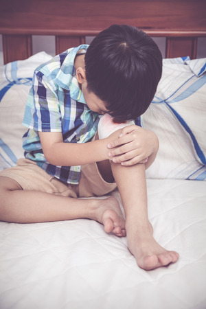 injurious: Childhood accidents. Sadness asian boy worry about wound on his knee with bandage. Child injured on bed in bedroom. Human health care and medicine concept. Vintage tone effect. Stock Photo