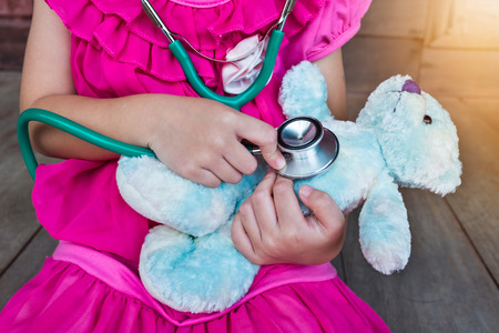 plush toy: Child playing doctor or nurse with plush toy bear with bright sunlight at home. Happy girl listens a stethoscope to toy. Playful girl role playing.