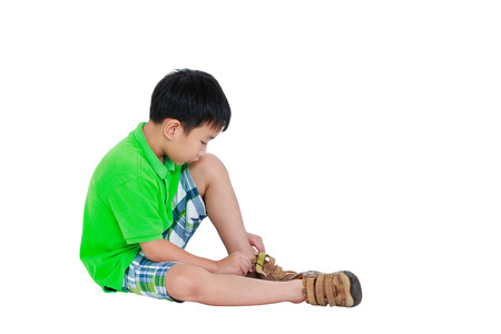 put on: Side view of cute asian child put leather shoes on. Boy sitting on floor. Isolated on white background and free form copy space. Studio shot. Positive human emotion.