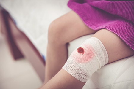 Child injured. Closeup wound on the childs knee with bandage. Shallow depth of field (DOF), selective focus, bandage in focus. Human health care and medicine concept. Vintage tone effect. Stock Photo