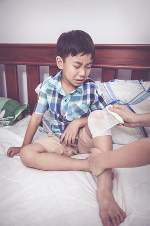 injurious: Crying child injured. Mother bandaging sons knee on bed inside bedroom, bandage in focus, asian boy sadden and crying. Human health care and medicine concept. Vintage tone effect.