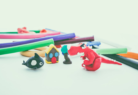 creative shot: Creative clay animal model. Red dinosaur, whale, house and tree from children bright play dough. Studio shoot. Vintage tone effect.