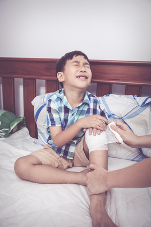 injurious: Child injured. Mother bandaging sons knee on bed inside bedroom, bandage in focus, asian boy sadden and crying. Human health care and medicine concept. Vintage tone.