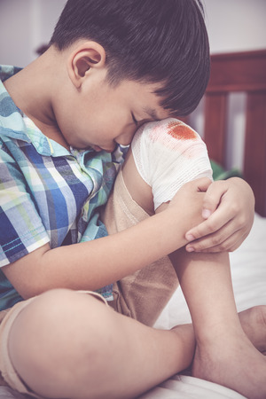 Childhood accidents. Sadness asian boy worry about wound on his knee with bandage. Child injured on bed in bedroom. Human health care and medicine concept. Vintage tone effect. Stock Photo