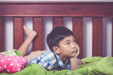 unhappiness: Sad child inside bedroom. Handsome asian boy lying on his bed looking sad and lonely. Boy has a look of unhappiness on his face. Problem families concept. Vintage tone effect. Stock Photo
