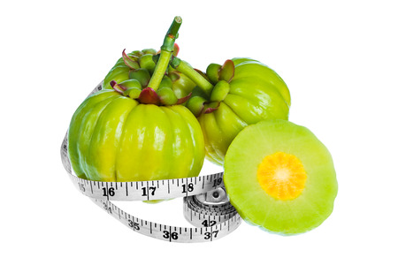 Garcinia cambogia fresh fruit with measuring tape, isolated on white background. Garcinia atroviridis is spice plants. It helps in the metabolism contain high vitamin C and hydroxy citric acids (HCA) Stock Photo