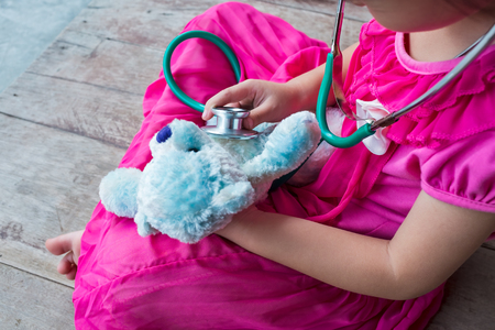 plush toy: Child playing doctor or nurse with plush toy bear at home. Happy girl listens a stethoscope to toy. Playful girl role playing.