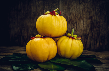 citric: Garcinia cambogia fresh fruit on wood background. Garcinia atroviridis is a spice plants and high vitamin C and hydroxy citric acids (HCA) for good health. Low key and high contrast style.