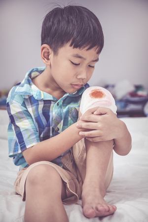 Child injured on bed in bedroom. Worry asian handsome boy looking at wound on his knee with bandage. Human health care and medicine concept. Vintage tone effect. Stock Photo