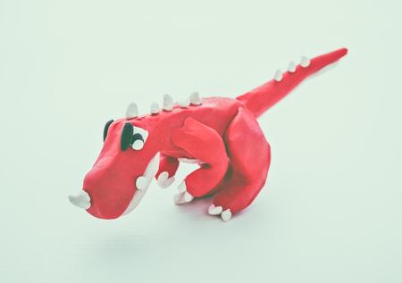 studio shot: Creative clay model. Red dinosaur from children bright play dough, on white background. Play dough animal. Studio shot. Vintage tone effect.