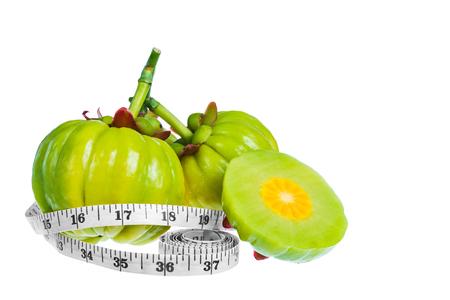 frescura: Garcinia cambogia fruta fresca con la cinta de medición, aislada en el fondo blanco. Garcinia atroviridis es plantas de especias. Ayuda en el metabolismo de los ácidos cítrico contienen altos hidroxi vitamina C y (HCA) Foto de archivo