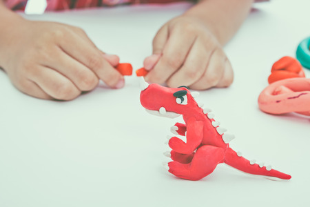 strengthen: Child playing and creating toys from play dough. Child molding model clay. Strengthen the imagination of child. Vintage tone effect. Stock Photo