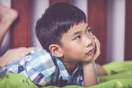 unhappiness: Closeup sad child inside bedroom. Handsome asian boy lying on his bed looking sad and lonely. Boy has a look of unhappiness on his face. Problem families concept. Vintage tone effect. Stock Photo