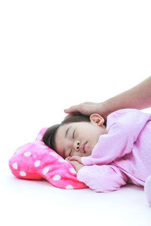 lovingly: Healthy children concept. Adorable asian child sleeping peacefully. Adorable girl in pink pajamas sleep tight on floor, isolated on white background. Mother put hand on daugyters head lovingly. Stock Photo