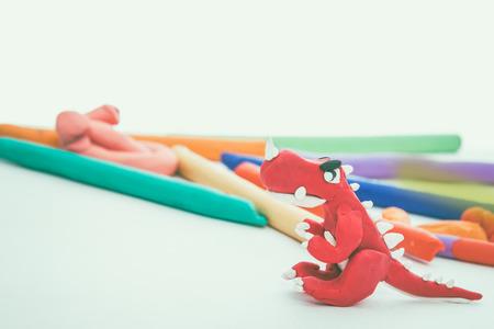 studio shot: Beautiful play dough animal. Creative clay animal model. Red dinosaur from children bright play dough. Studio shot. Vintage tone effect. Stock Photo