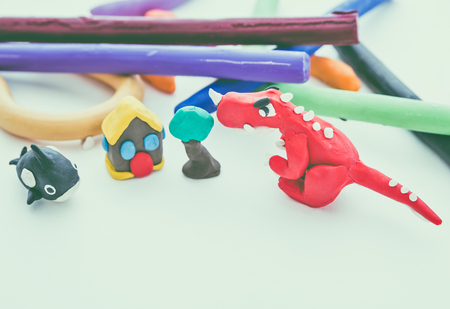 studio shot: Beautiful play dough animal. Creative clay animal model. Red dinosaur, whale, house and tree from children bright play dough. Studio shot. Vintage tone effect.