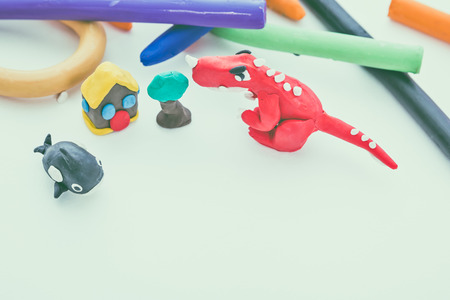 studio shot: Beautiful play dough animal. Creative clay animal model. Top view of red dinosaur, whale, house and tree from children bright play dough. Studio shot. Vintage tone effect.