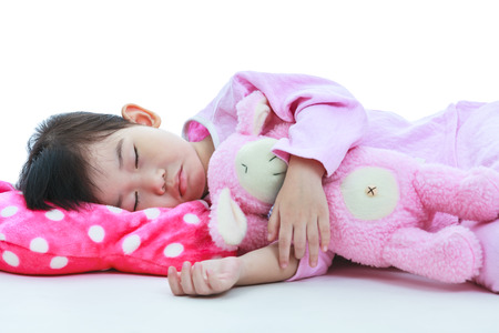 Healthy children concept. Closeup of asian child sleeping peacefully. Adorable girl in pink pajamas sleep tight on floor, on white background.