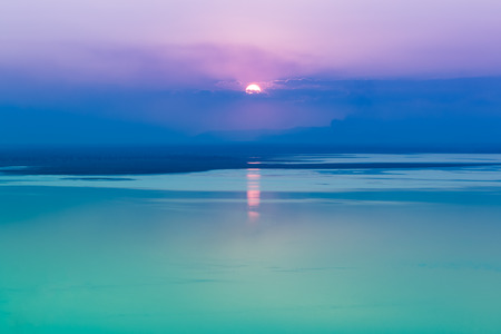 cool colors: Fantastic seascape with cool sunset background. Abstract beautiful sunrise over the sea. Bright seascape during sundown with reflection of sun. Outdoor. Cool colors tone effect.