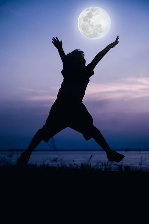 cool colors: Silhouette back view of child enjoying and jumping at riverside. Full moon with fantastic sky background. Happy time on vacation. Outdoor. Cool colors tone effect. The moon were NOT furnished by NASA.