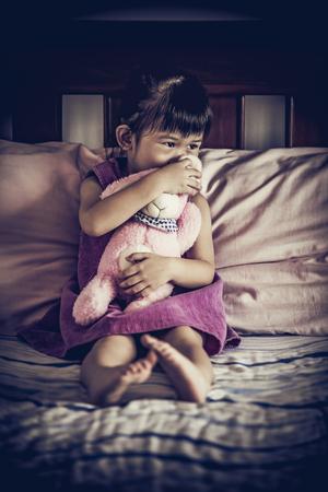 ni�os abandonados: Ni�o triste asi�tico sentado solo en la cama con la mu�eca en la habitaci�n oscura en casa. Emocional de la muchacha deprimida con una profundidad de campo, enfoque selectivo. estilo de vi�eta. Bajo llave y alto efecto de contraste. Foto de archivo