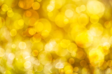 Defocused bokeh. Twinkling light gold bokeh abstract background for Christmas and Happy new year holiday. Festive elegant blurred background with glod bokeh circular and bright light.