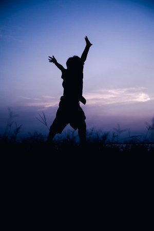 cool colors: Silhouette back view of child enjoying and jumping at meadow. Fantastic of sky background. Happy time on vacation. Abstract beautiful nature background. Outdoor. Cool colors tone photo effect.