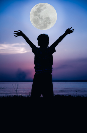 Silhouette back view of child enjoying the view at riverside. Full moon with fantastic sky background. Boy raising his hands up. Outdoor. Cool colors tone effect. The moon were NOT furnished by NASA. Stock Photo