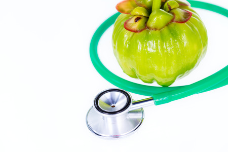 citric: Garcinia cambogia fresh fruit and stethoscope, on white. Garcinia atroviridis is a spice plants and high vitamin C and hydroxy citric acids (HCA) for diet and good health. Stock Photo