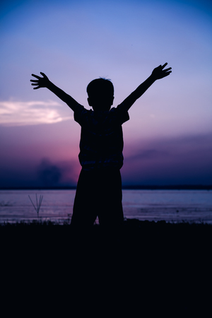 cool colors: Silhouette back view of child enjoying the view at riverside. Fantastic of sky background. Boy raising his hands up. Abstract beautiful nature background. Outdoor. Cool colors tone photo effect.