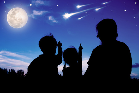 Silhouette of mother and two kids sitting and looking sky with comets. Colorful blue sky and bright full moon background. Friendly family. The moon were NOT furnished by NASA.