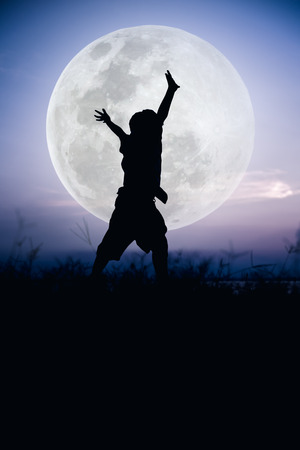 cool colors: Silhouette back view of child enjoying and jumping. Large full moon with fantastic sky background. Happy time on vacation. Outdoor. Cool colors tone effect.