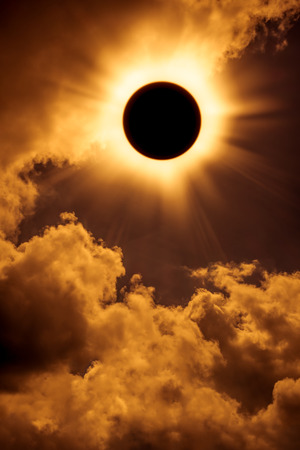 solar eclipse: Solar eclipse space with cloud. Abstract fantastic background - full sun solar eclipse glowing on sky and cloudy orange background. Outdoors.