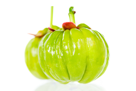 citric: Garcinia cambogia fresh fruit with reflection, on white background. Garcinia atroviridis is a spice plants and hydroxy citric acids (HCA) for good health. Shallow depth of field, selective focus.