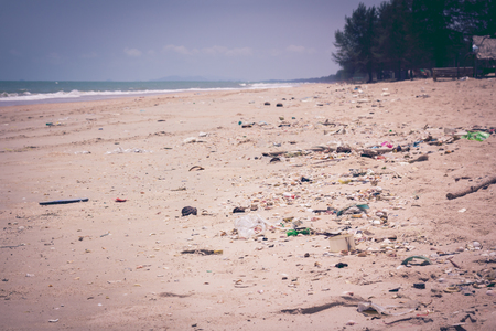 Pollution on the beach of tropical sea. Plastic garbage, foam, rubbish and dirty waste on beach in summer day. Clear sky on a bright sunny day, outdoors at the daytime. Vintage tone effect.