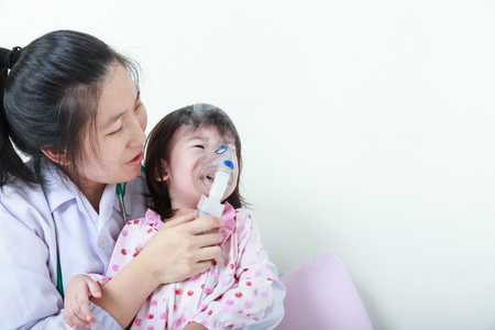 Sad asian child having respiratory illness helped by doctor with inhaler. Pediatrician take care girl with asthma problems making inhalation with mask at hospital. child was bronchitis and crying.