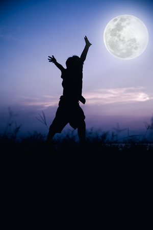 cool colors: Silhouette back view of child enjoying and jumping at meadow. Full moon with fantastic sky background. Happy time on vacation. Outdoor. Cool colors tone effect. The moon were NOT furnished by NASA.
