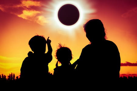 solar eclipse: Silhouette back view of family sitting and relaxing together. Boy point to solar eclipse on gold sky background. Happy family spending time together. Outdoor.