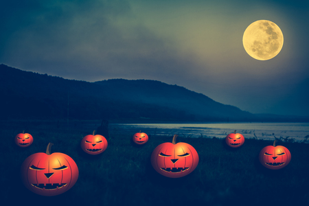 Background for Halloween holiday. Mountain and bright full moon at night. Pumpkins with scary face on the riverbank. Outdoors. Cross process and vintage tone effect.The moon were NOT furnished by NASA