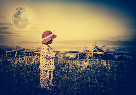 full moon effect: Asian child relaxing outdoors with bright full moon at night, travel on vacation. Adorable girl in night sky under beautiful full moon. Vintage tone effect. The moon were NOT furnished by NASA.