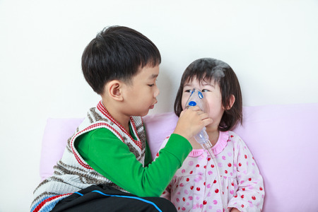 Asian child was bronchitis and crying. Kindly brother take care his sister with asthma problems making inhalation by mask at hospital. Happy family concept, loving and bonding of sibling. Banque d'images