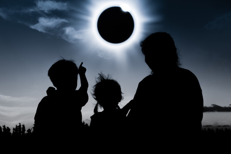 natural phenomenon: Natural phenomenon. Silhouette back view of mother and child sitting and relaxing together. Boy pointing to solar eclipse on dark sky background. Happy family spending time together. Outdoor.