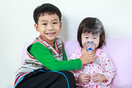 nursing sister: Asian child was bronchitis and crying. Kindly brother smiling and take care his sister with asthma problems making inhalation by mask at hospital. Happy family concept, loving and bonding of sibling.